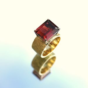 Octagonal cut red tourmaline set in white gold on 18ct textured band