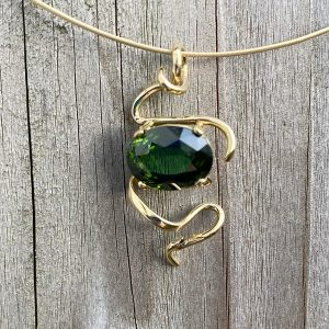 Oval cut green tourmaline set in twist pendant on cable chain all in 18ct gold