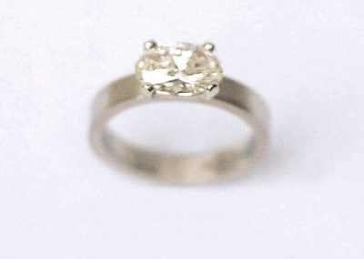 1.5ct oval cut diamond set in platinum flat band style engagement ring