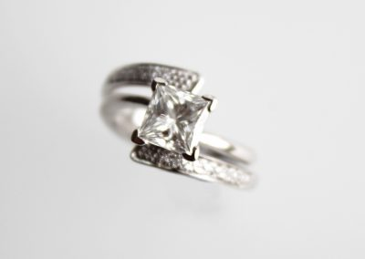 Princess cut and pave diamonds set in platinum wrapped spike style engagement ring