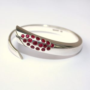 Hand forged silver bangle with inlaid rubies